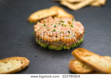 Classic salmon tartare is made with chopped fresh raw salmon fish, avocado, tartar sauce and crackers or bread. This healthy dish is often served as appetizer in fine dining restaurants.