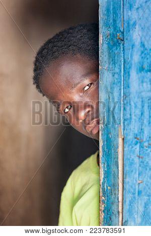 African child standing behind a door in the village, Botswana