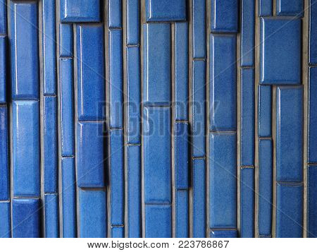 Ceramic brick pattern background photograph, vertical blue glazed bricks. Abstract pattern of ceramic bright blue brickwork, authentic photograph shot outdoors with natural light shading.