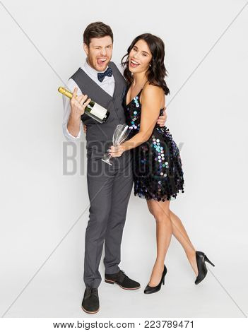 celebration and holidays concept - happy couple with bottle of non alcoholic champagne and wine glasses at party