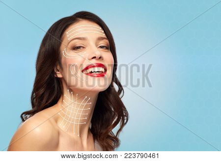 beauty and anti-age concept - happy young woman with lifting arrows on face and neck skin over blue background