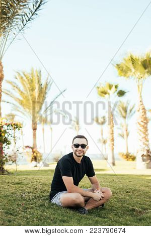 Handsome Bearded Man In Sunglasses Sitting On The Grass Under Palms On Summer Vocation.