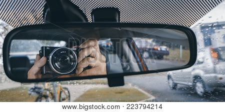 Canberra, Australia - Apr 26, 2017: Hand holding a camera while pointing to car's rear view mirror. Unconventional hidden self-portrait pose. Light rain in forward view.