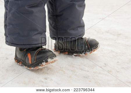 a child walks on the street.  winter. cold. legs.  boots. close-up.
