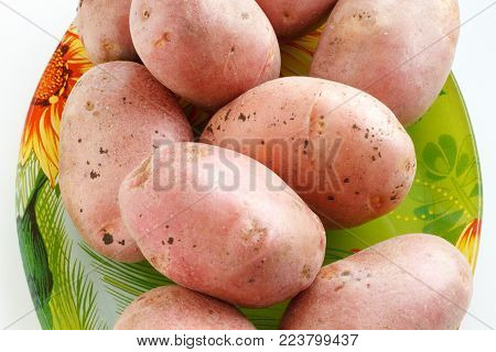 A lot of potatoes. A lot of potatoes lying on the plate. The potatoes on the plate and scattered on the table. The harvest of potatoes. Vegetables for a healthy diet.