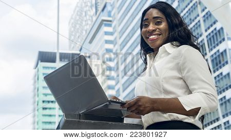 Portrait of happy business african woman uses computer laptop in the outdoor with the city space background