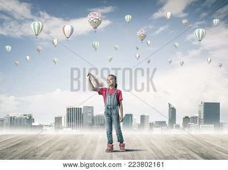 Cute kid girl standing on wooden floor and aerostats flying in air