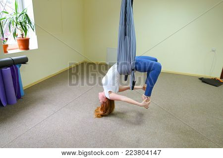 Beautiful girl of American appearance performs acrobatic elements in air, child concentrates and calmly holds on acrobatic ropes. Room nice warm lighting, walls delicate yellow and large windows, on windowsill pots with flowers, under wall  folded rugs fo