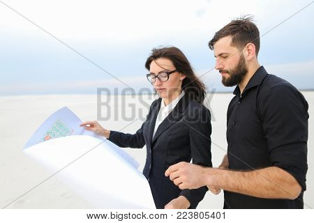 CEO male and CFO female holding whatman paper, colleagues discuss project of wind power plant in deserted place. Young woman and bearded guy standing among sands looking around. Concept of exploring new territories and designing or alternative energy sour