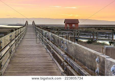 Wooden Bridge and Cabin Landscape. Sunset at Don Edwards San Francisco Bay National Wildlife Refuge, Fremont, Alameda County, California, USA.