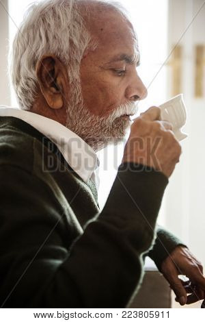 Senior indian man sipping hot drink