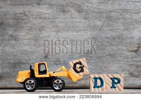 Yellow plastic bulldozer hold letter G to complete word GDP (Abbreviation of Gross Dometsic Product or Good Distribution Practice ) on wood background