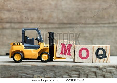 Toy yellow forklift hold letter block M to complete word MOQ (Abbreviation of Minimum Order Quantity)on wood background