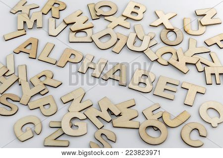 The word alphabet in wooden letters diagonally placed with loose wooden letters around it.