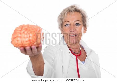 female doctor is holding an plastic brain, looking to the viewer,  isolated in front of white