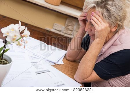 senior adult with lot of documents on a table