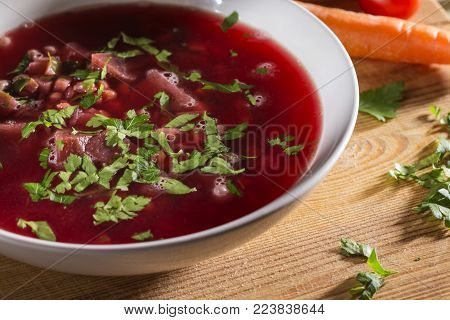 Traditional Romanian beet borscht in white bowl on wooden cutting board