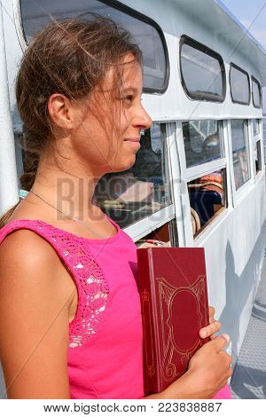 The girl with dreamy gaze and  book in his hand is traveling on white ship.