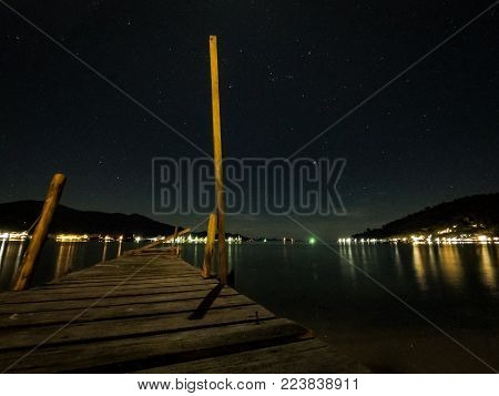 Stars at sky with wooden jetty at the beach
