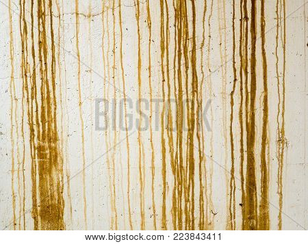 Rust stain runs, natural abstract background photograph. Brown rust stains streaked down a white painted concrete wall. Natural thin brown jagged stripes, drawn by gravity with city grunge appeal.