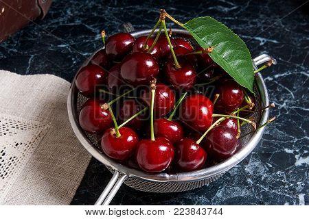 Fresh Organic Cherry In Yellow Wooden Basket On Dark Marble Background.