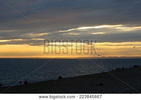 anglers fishing on Chesil Bank at sunset