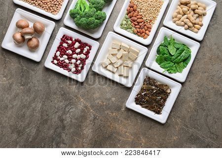 Set of various vegan protein sources, assortment of vegan protein rich alimentary products such as tofu, legumes, nuts, seaweeds and other, view from above, flat lay, space for a text