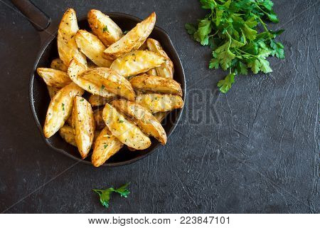 Baked potato wedges with cheese and herbs and tomato sauce on black background - homemade organic vegetable vegan vegetarian potato wedges snack food.