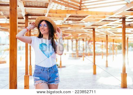 Young Beautiful Happy Woman In A Hat And Sunglasses Stands On The Sand In A Beach Cafe. Travel, Trop