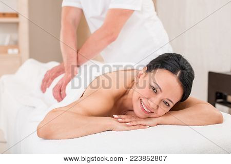 Masseur giving glad mature woman a massage. Relaxed lady smiling and lying on the couch in beauty salon. She is looking at camera