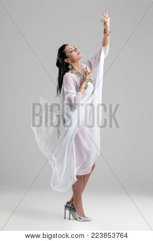 Sensual oriental belly dancer dancing, grey background