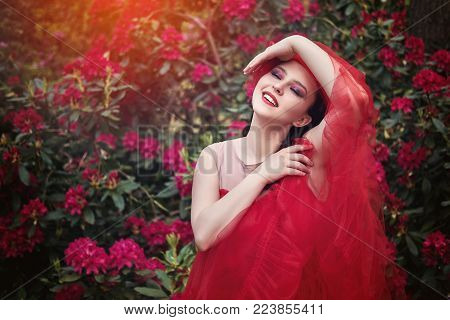 beautiful young woman with pretty hairstyle and bright makeup standing in rhododendron flowers garden. outdoor summer shot. copy space.