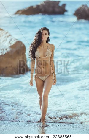 Romantic young girl in bikini outdoors against tropical background. Close-up portrait of beautiful sensual brunette mixed race Asian Caucasian woman walking fwom water on the beach. Slim female model resting on the sea shore.