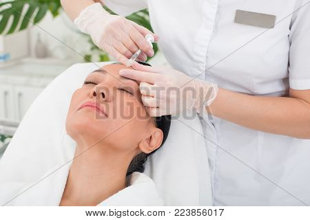 Tense asian woman lying on the couch with closed eyes in beauty salon. Doctor is giving an injection to strained lady