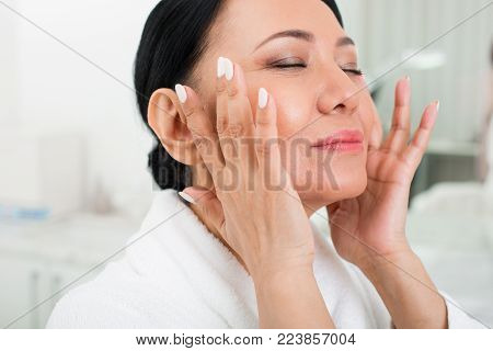 Feeling good. Calm senior woman using cosmetic at spa. She is rubbing the cream with her finger. Her eyes are closed