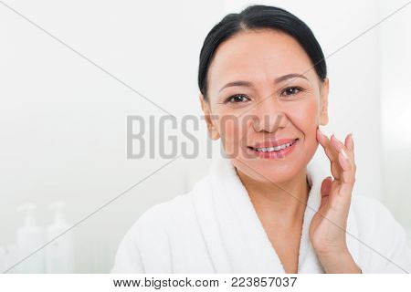 Portrait of middle-aged asian woman looking at camera. She is smiling and feeling her skin at spa. Copy space in left side