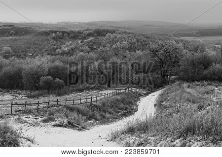 Winter Black And White Landscape. Dirt Winding Road Among The Hills. Trees Covered With Hoarfrost. F