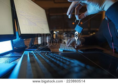 Close up hand of computer burglar downloading secret information from digital device while holding clues. Theft concept