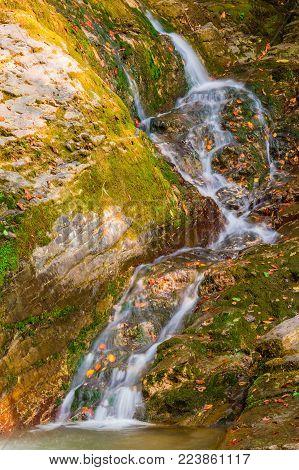 The cascade waterfall of the mountain river Bezumenka closeup in sunny autumn day, Sochi, Russia