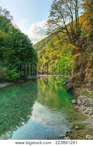 The valley of Sochi River with rocky walls and thicket with varicolored trees in sunny autumn day, Sochi, Russia