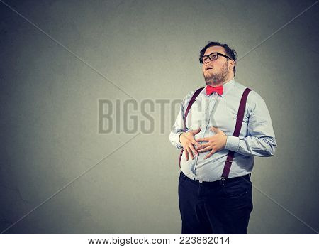 Irritated man with overweight wearing glasses and formal clothing having digestive trouble.