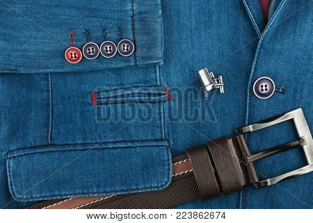 Elegant denim suit with a silver cufflinks and belt. Male jacket with cufflinks and pockets, close-up. Men's fashion. View from above.