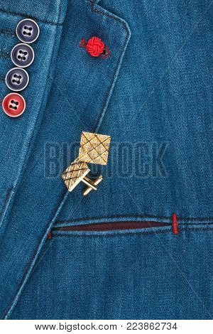 Elegant denim suit with a gold cufflinks. Male jacket with gold cufflinks and pocket, close-up. Men's fashion. View from above.