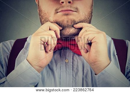 Crop chubby man in bow tie showing second chin suffering from obesity.