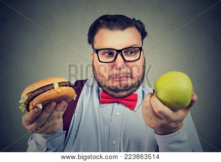 Overweight man holding hamburger and green apple having problems with diet choice.