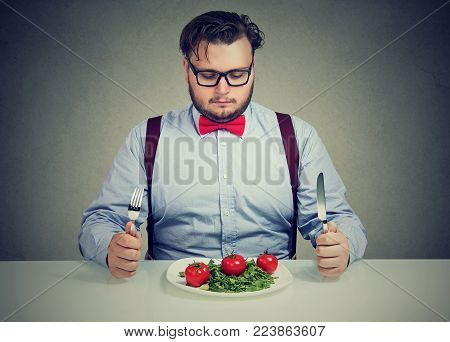 Young overweight man concentrated on healthy salad trying to lose weight.