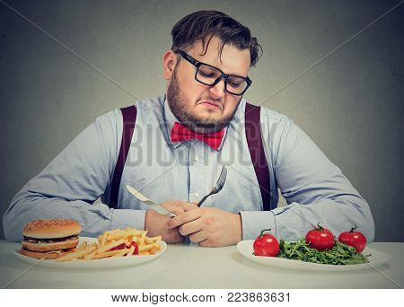 Overweight man in formal outfit looking at salad†with hate while craving juice hamburger.
