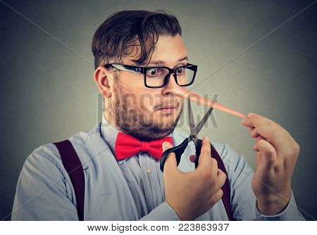 Chubby man having long nose of liar trying to cut it off and change situation.