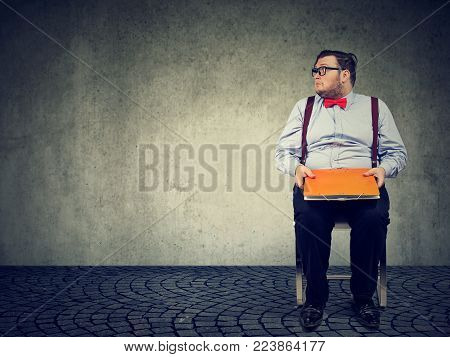 Young chubby man sitting with file waiting for job interview looking nervous.