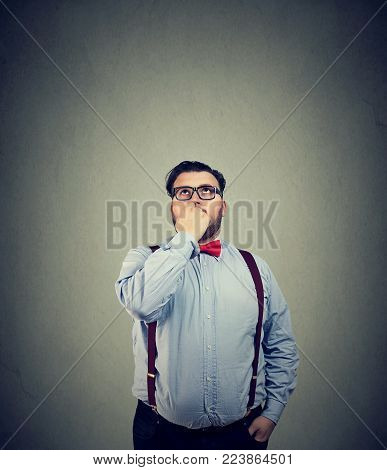 Young man in eyeglasses looking up and thinking thoroughly making important decision.